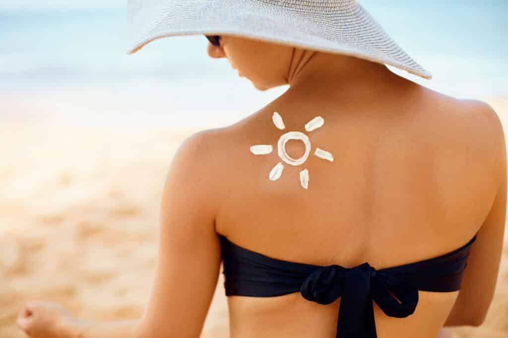 Sun cream on tanned shoulder. Sun protection. Beautiful woman in bikini applying Solar Cream. Skin and body care. Portrait of female holding suntan lotion and moisturizing sunblock.